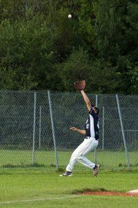 Ein Feldspieler fängt einen geschlagenen Ball aus der Luft