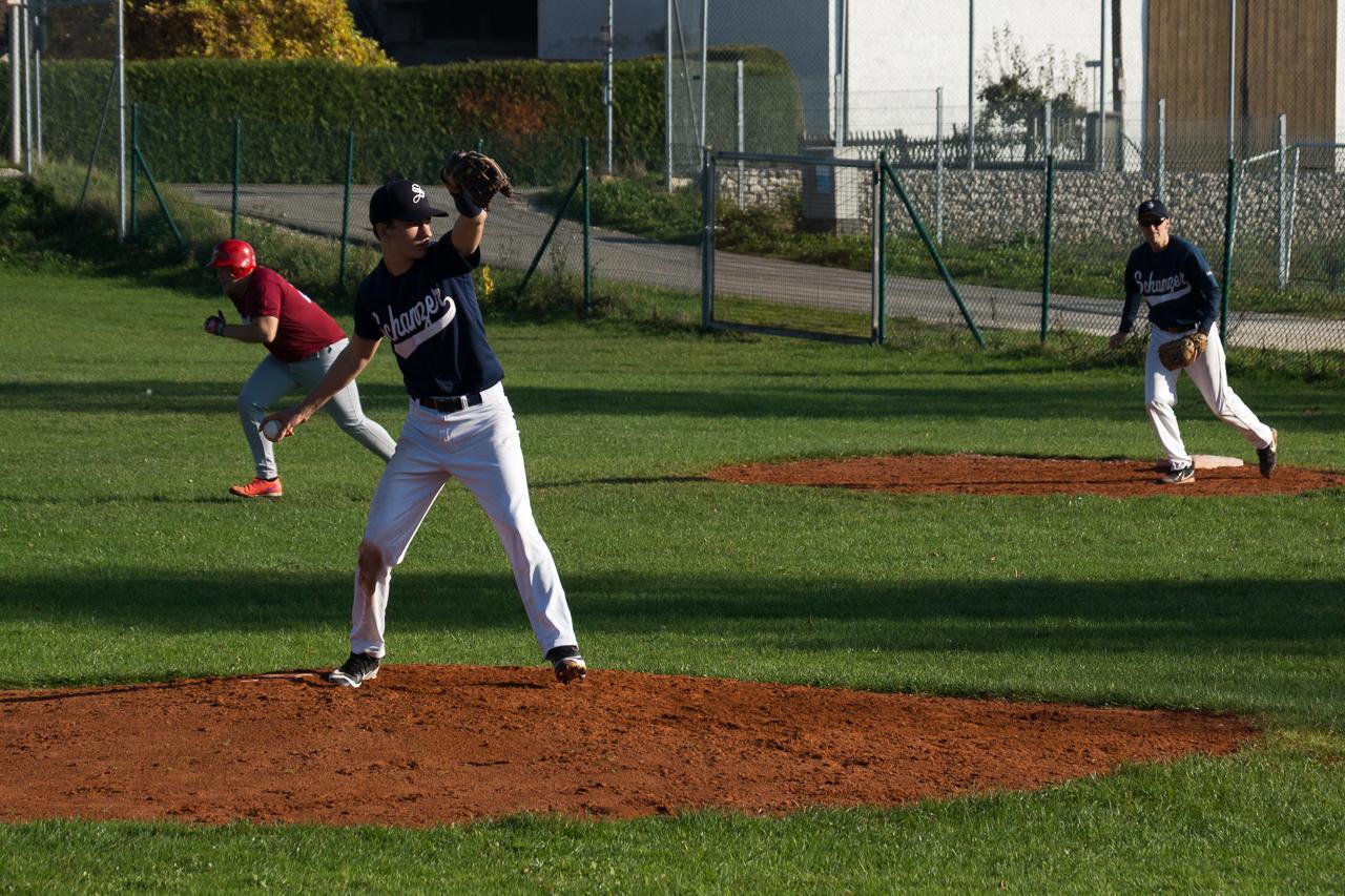 Pitcher beim Wurf, im Hintergrund läuft ein Läufer von der ersten zur zweiten Base.